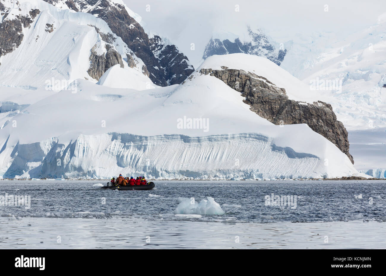 Heavily glaciated landscapes reach out to passengers cruising in a Zodiak in Wilhelmina Bay.  Gerlache Strait, Antarctic - Stock Image