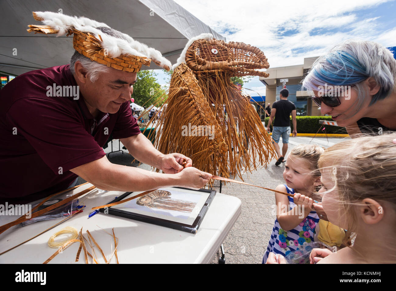 A first nation weaver works with cedar strips and a little help from a young onlooker during Canada Day celebrations - Stock Image
