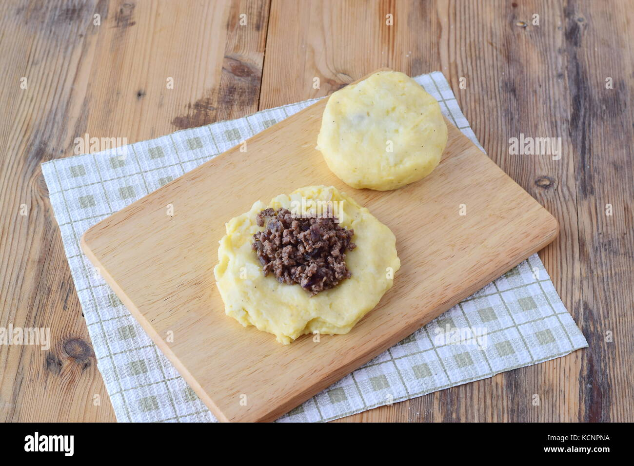 Potato dumplings stuffed with minced meat on a wooden cutting board. Step by step cooking. Healthy eating concept - Stock Image