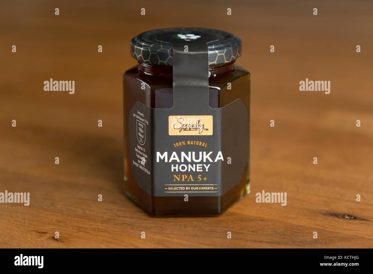 A jar of Aldi Specially Selected Manuka honey is shot against a wooden background (Editorial use only). - Stock Image