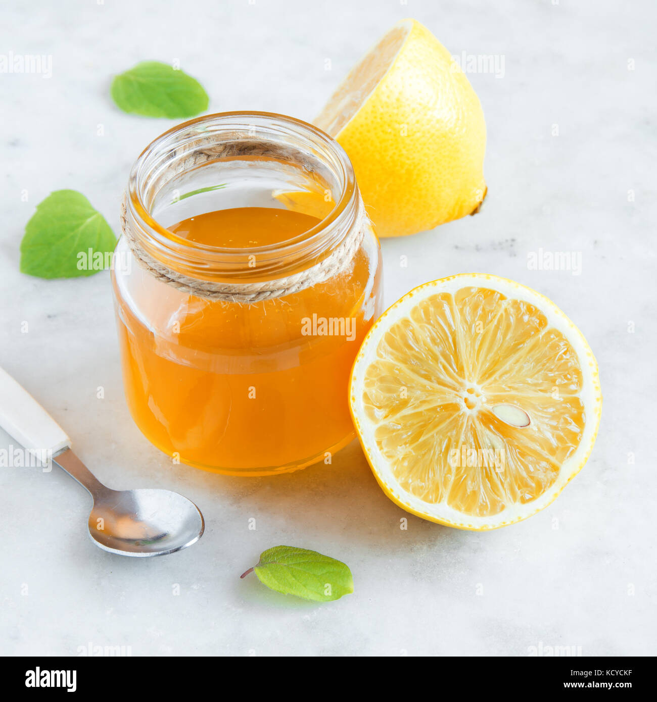 Lemon and honey over white stone background with copy space - healthy organic products for alternative medicine - Stock Image