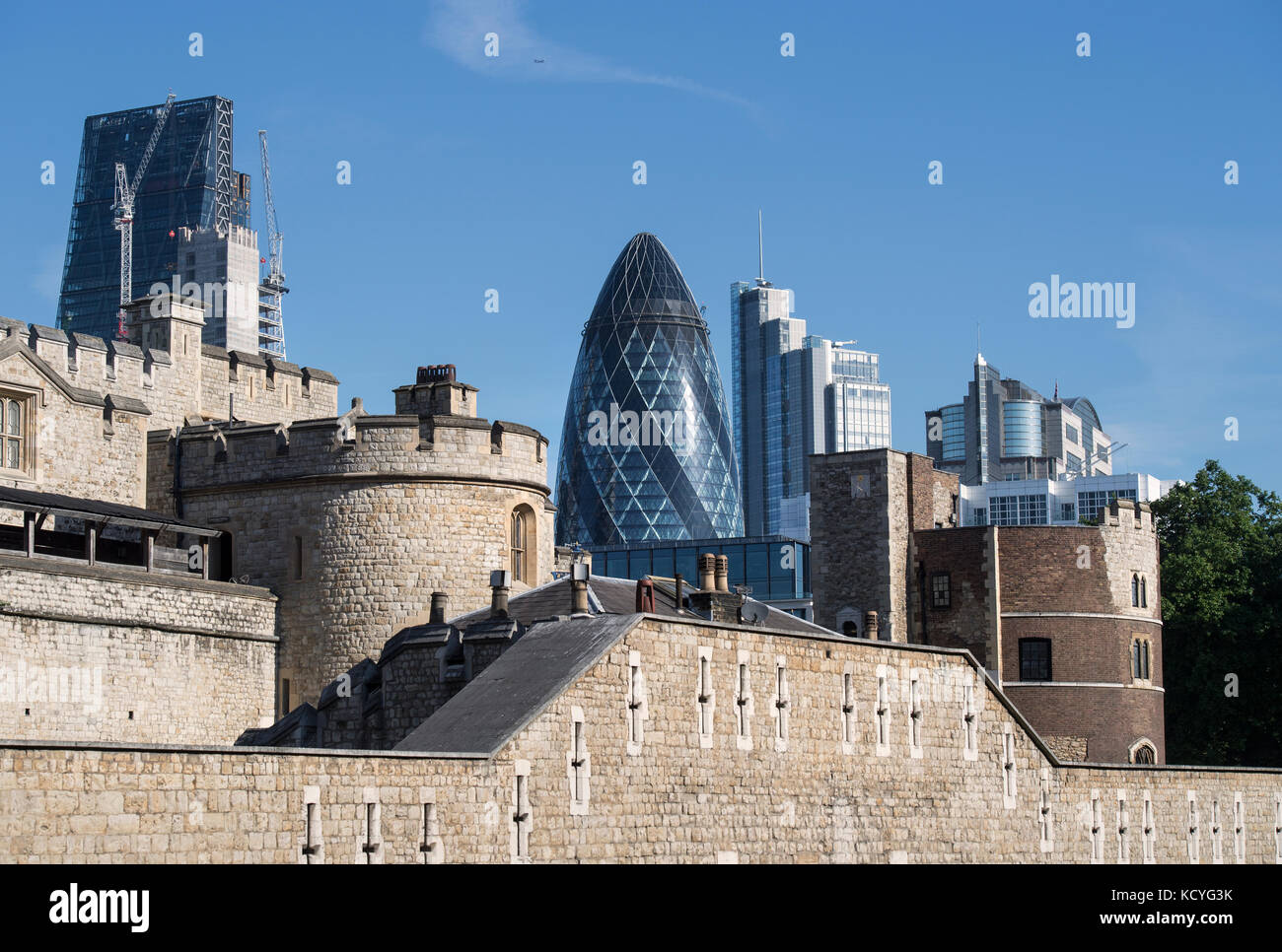 Walls of the Tower of London in London, England, UK, with the Gherkin building in the background - Stock Image
