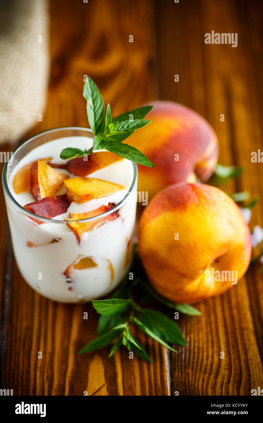 Sweet home-made yogurt with pieces of peach - Stock Image