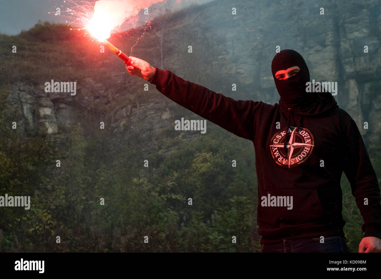 Eastern European Football Hooligan Stands with a lit flare gun. - Stock Image