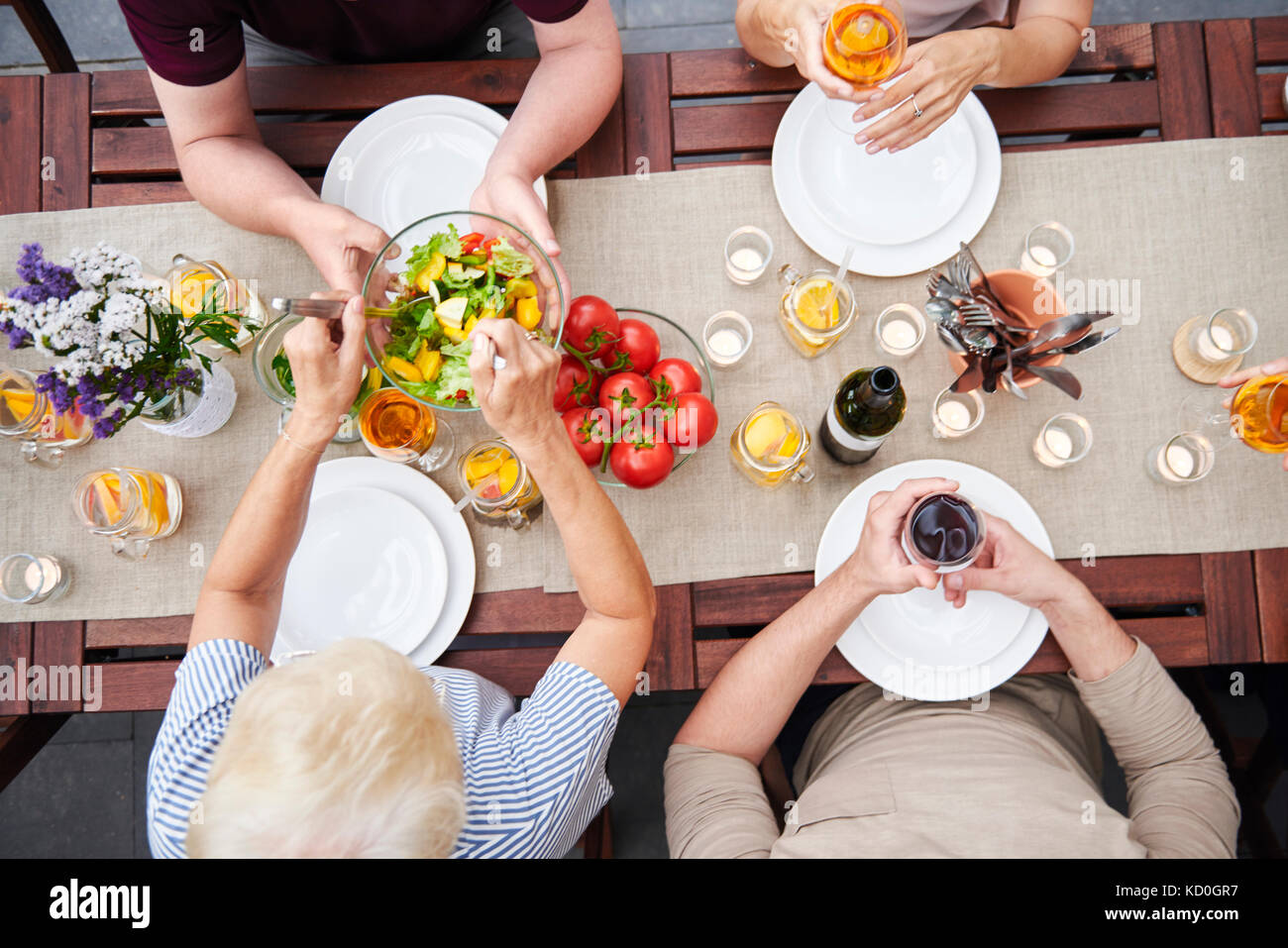 Overhead view of family handing salads at family lunch on patio - Stock Image