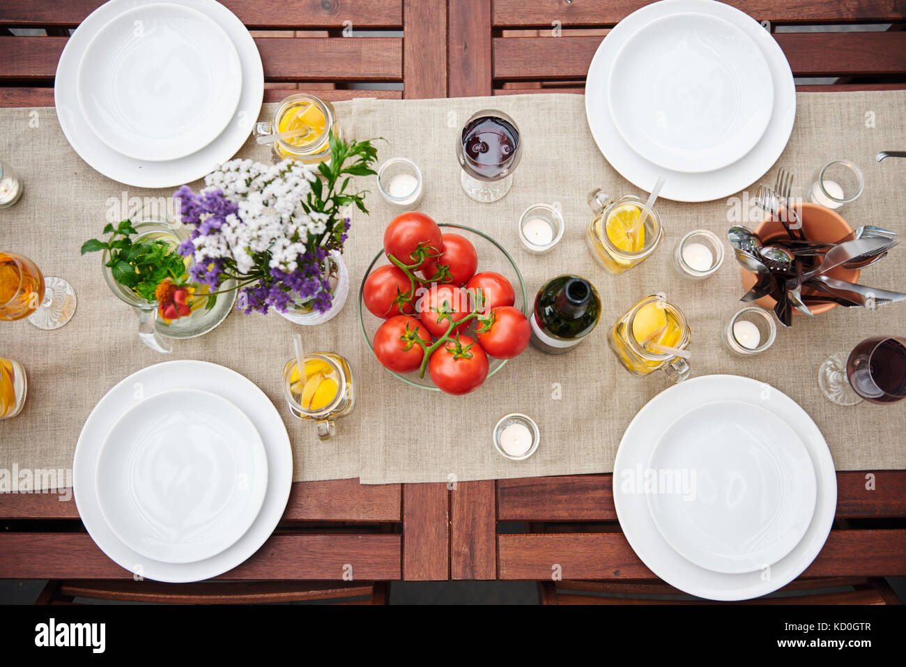 Overhead view of table prepared with flowers and vine tomatoes for lunch on patio - Stock Image