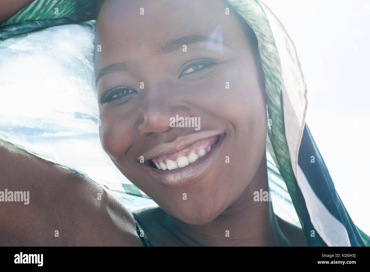 Portrait of young woman on beach, smiling, sheer scarf draped around her, close-up - Stock Image