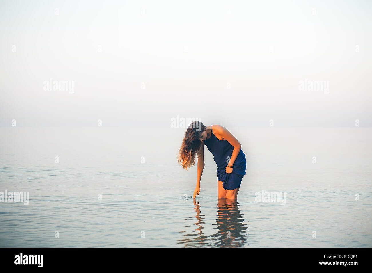 Young woman knee deep in sea touching surface, Odessa, Ukraine - Stock Image