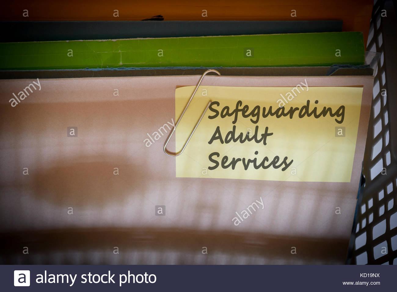Safeguarding Adult Services written on document folder, Dorset, England. - Stock Image