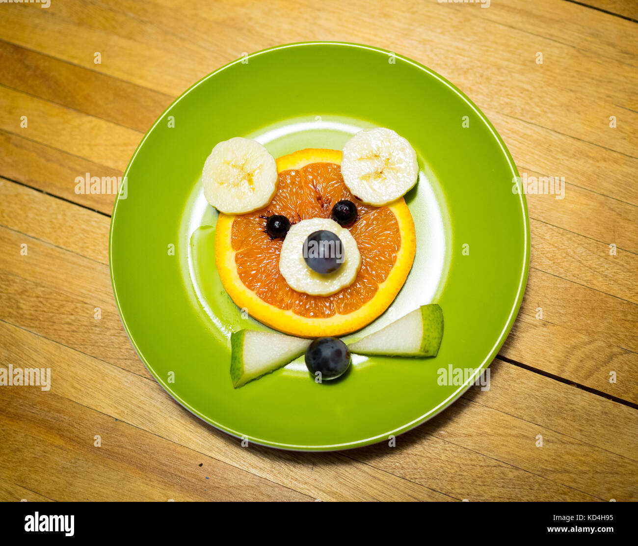 Bear food art for kids. (Food art fruit bear).  Made from orange, banana, blueberries, grapes, and pear. - Stock Image