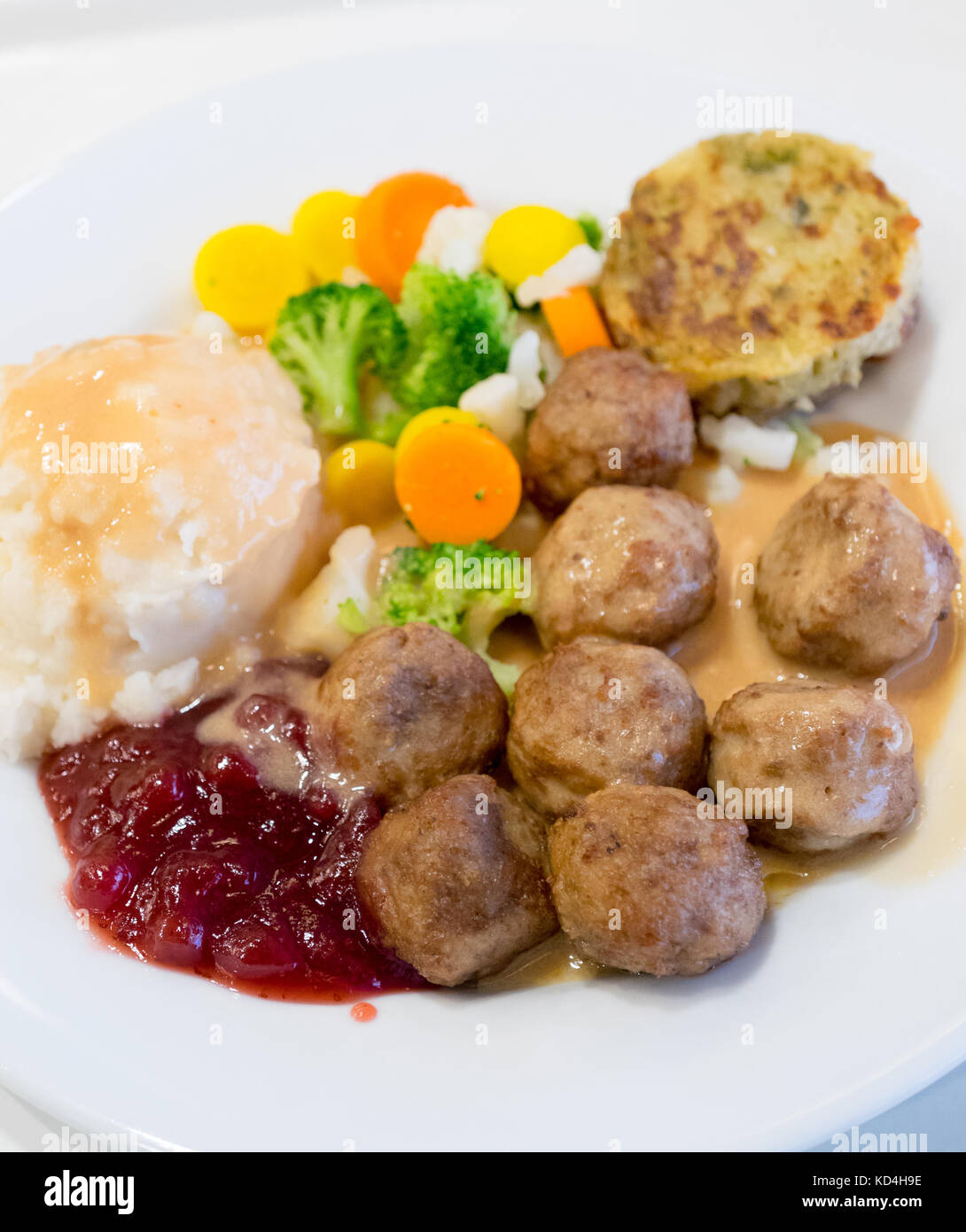 A plate of IKEA meatballs, mashed potatoes, cream gravy, lingonberry sauce, mixed vegetables and a potato-vegetable - Stock Image