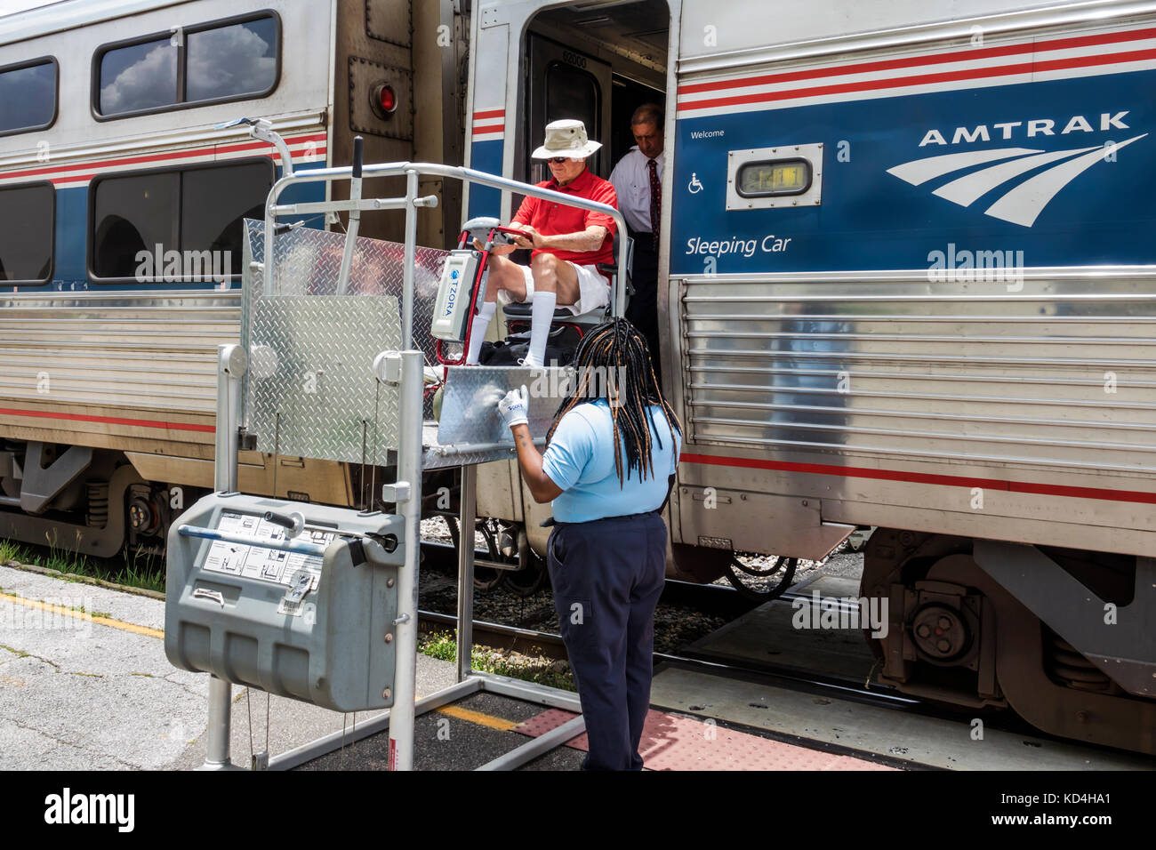 Florida Orlando station railroad train Amtrak stop Black man woman passenger disabled wheelchair lift assisting - Stock Image