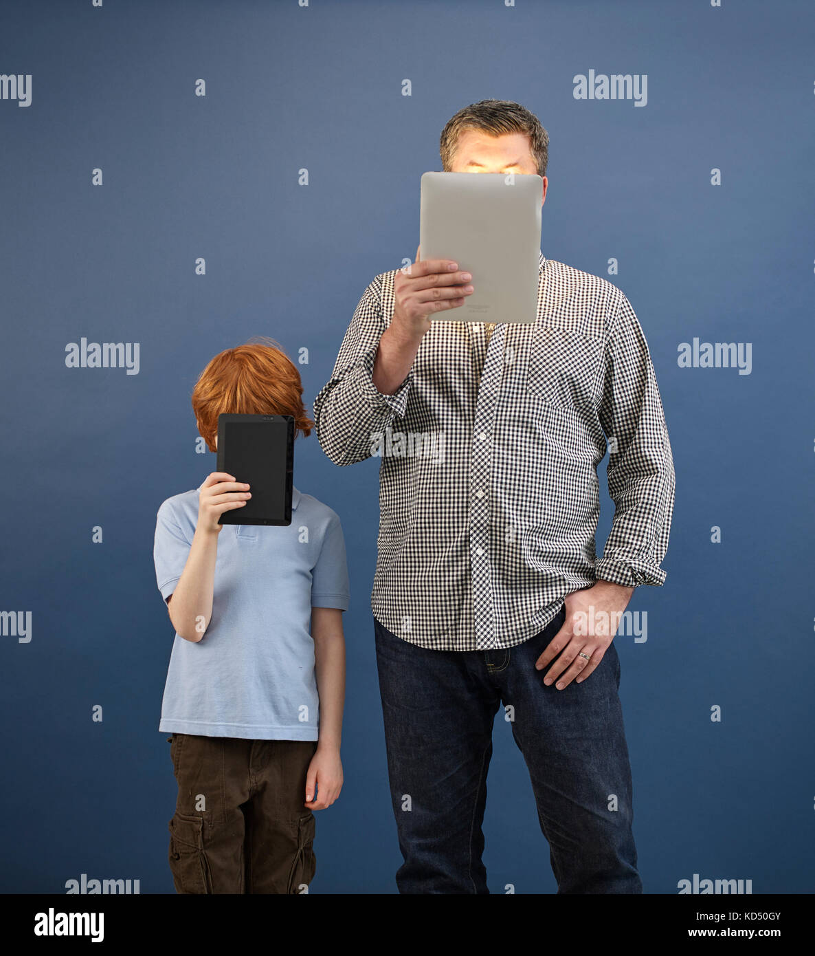adult and child looking at tablets - Stock Image