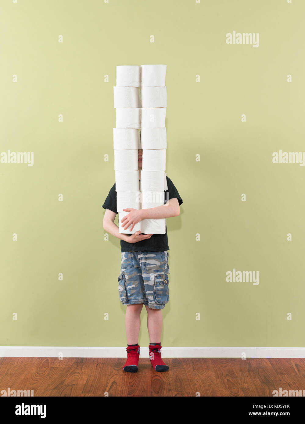 boy 4-7 balancing two stacks of toilet paper - Stock Image