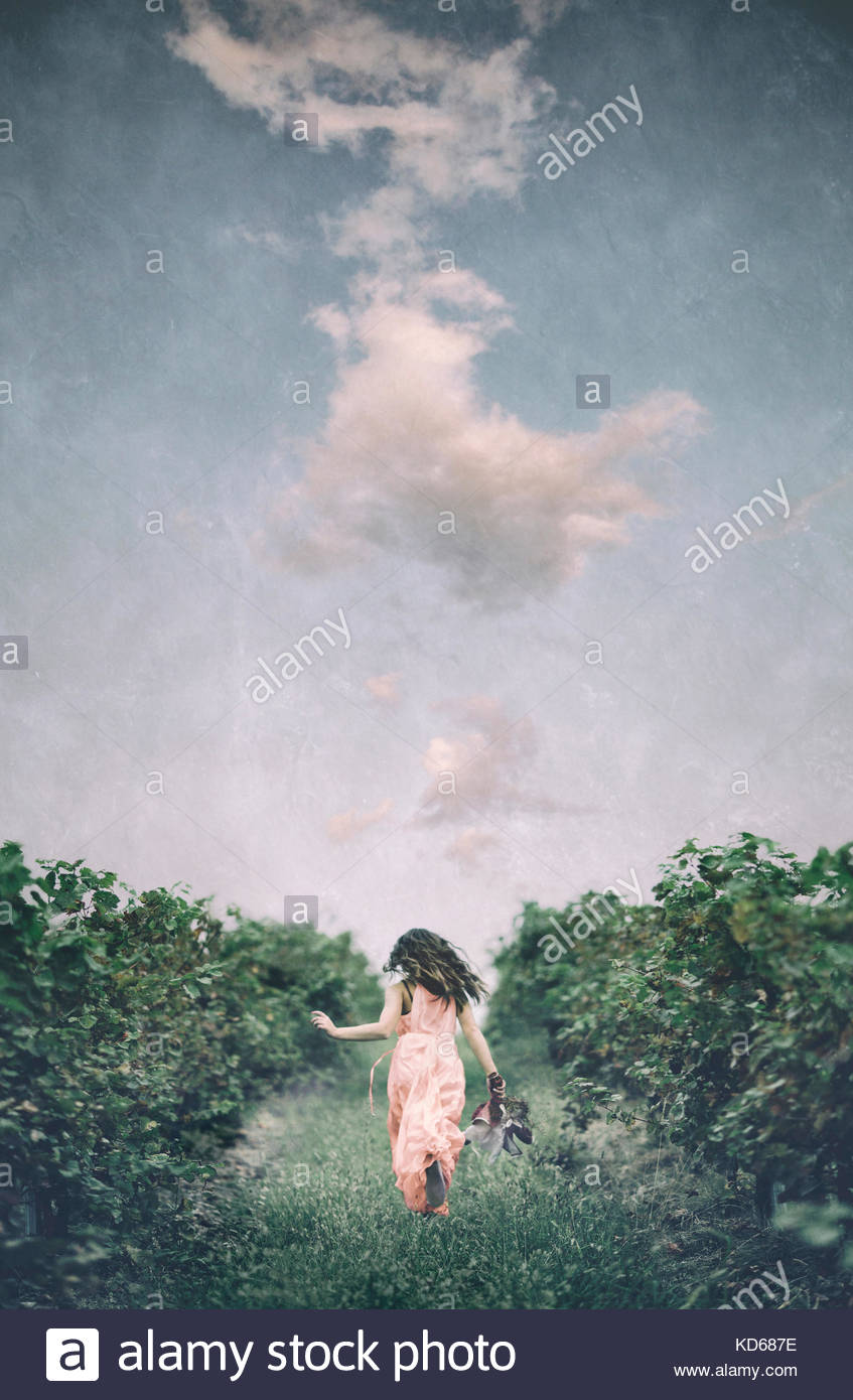 Girl running in a vineyard, holding a rag doll. Dramatic sky. - Stock Image