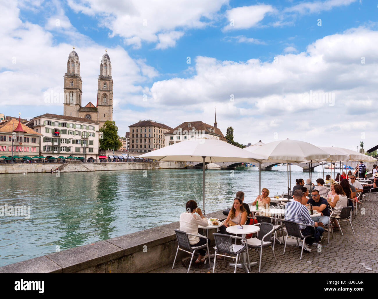 Cafe on the banks of the River Limmat looking towards the Grossmünster, Zürich, Lake Zurich, Switzerland - Stock Image