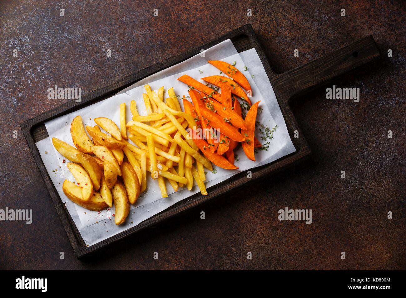 Variety of potatoes for garnish: potato wedges, french fries, sweet potato on brown background - Stock Image