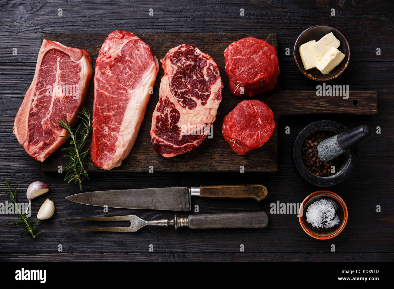 Variety of Raw Black Angus Prime meat steaks Blade on bone, Striploin, Rib eye, Tenderloin fillet mignon on wooden - Stock Image