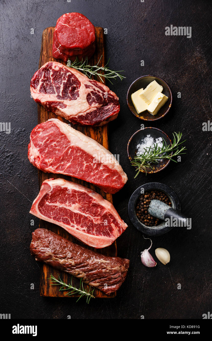 Variety of Raw Black Angus Prime meat steaks Machete, Blade on bone, Striploin, Rib eye, Tenderloin fillet mignon - Stock Image
