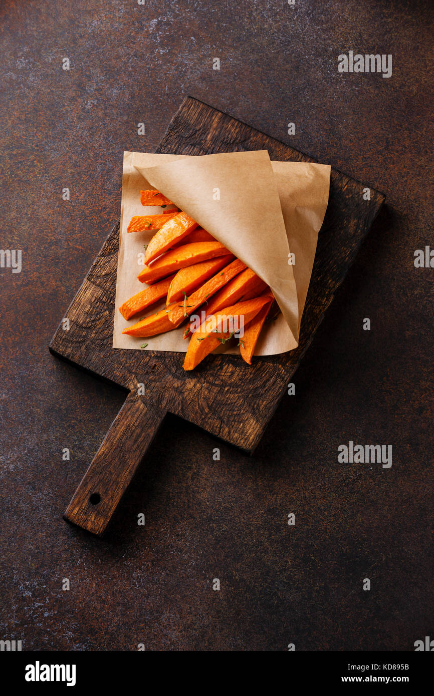 Sweet potato wedges for garnish on wooden cutting board on brown background - Stock Image