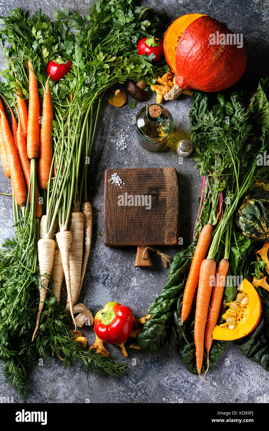 Variety of autumn harvest vegetables carrot, parsnip, chard, paprika, hokkaido pumpkin, mushrooms. Empty wooden - Stock Image