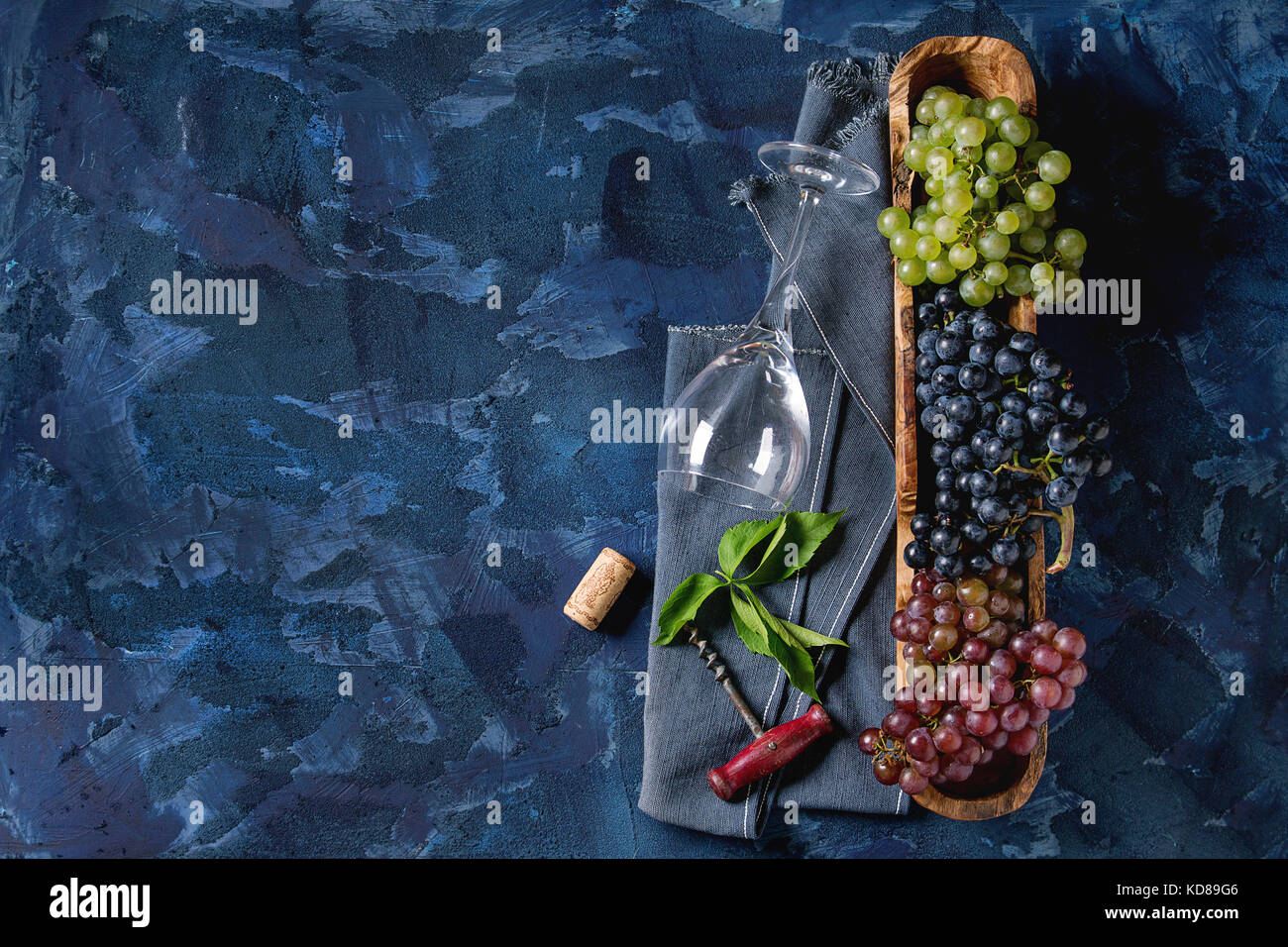 Variety of three type fresh ripe grapes dark blue, red and green in wooden bowl with empty laying wine glass, old - Stock Image