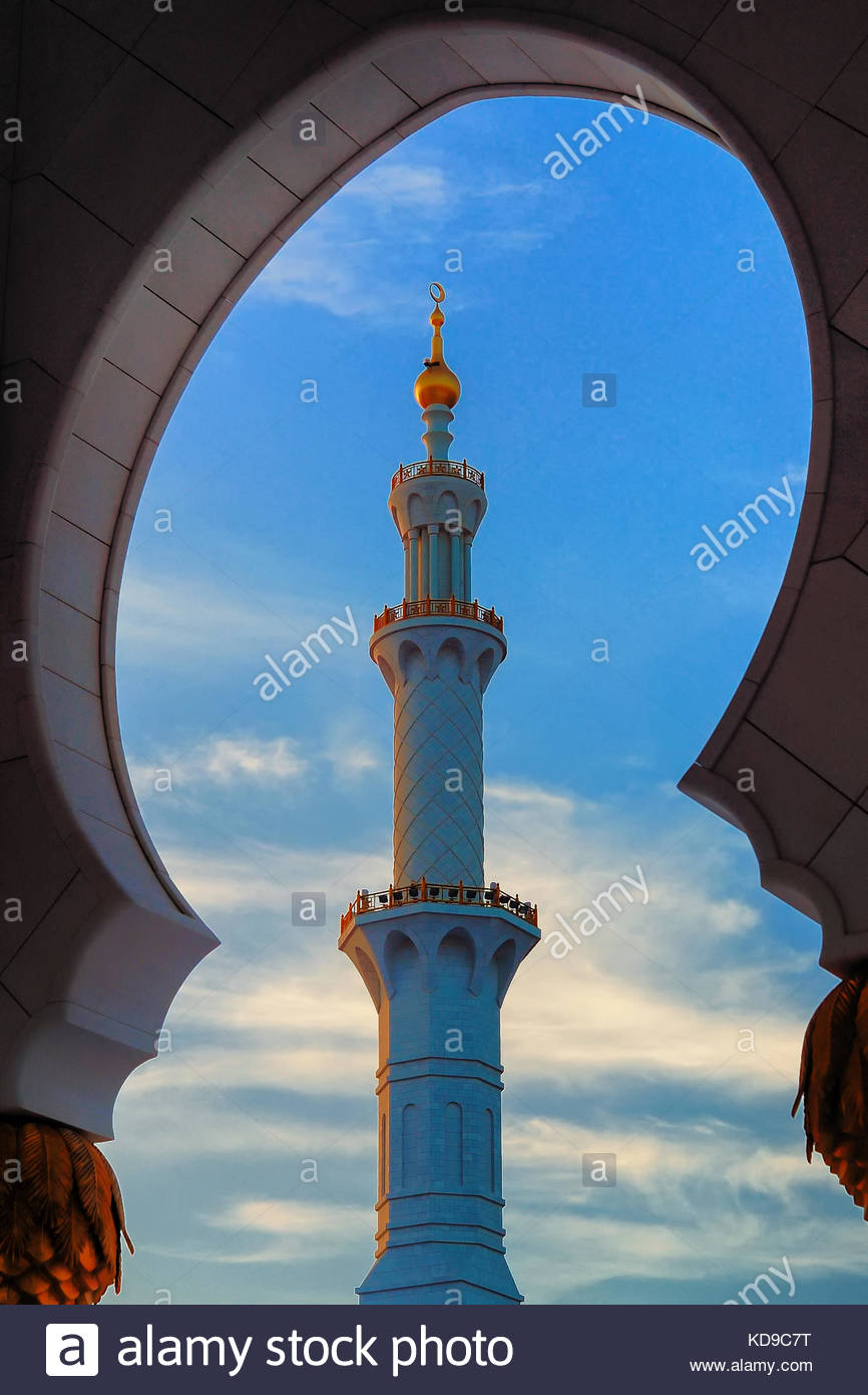 Detailed view at minaret of Mosque, Abu Dhabi, United Arab Emirates. Typical sunset sky with colorful clouds - Stock Image