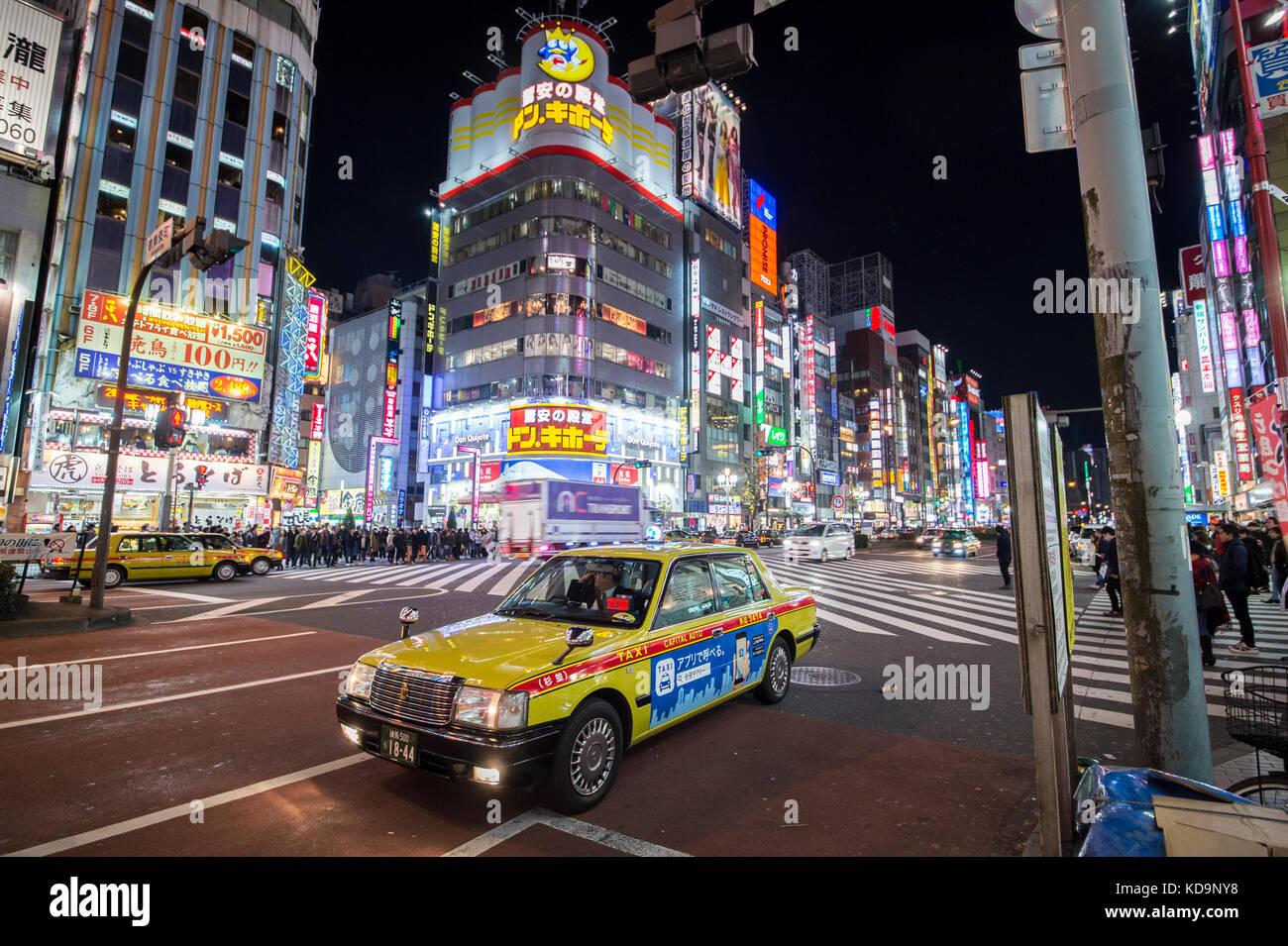 TOKYO - DECEMBER 31, 2016: A taxi driver is waiting for a passenger in Shinjuko district in Tokyo at night. December - Stock Image