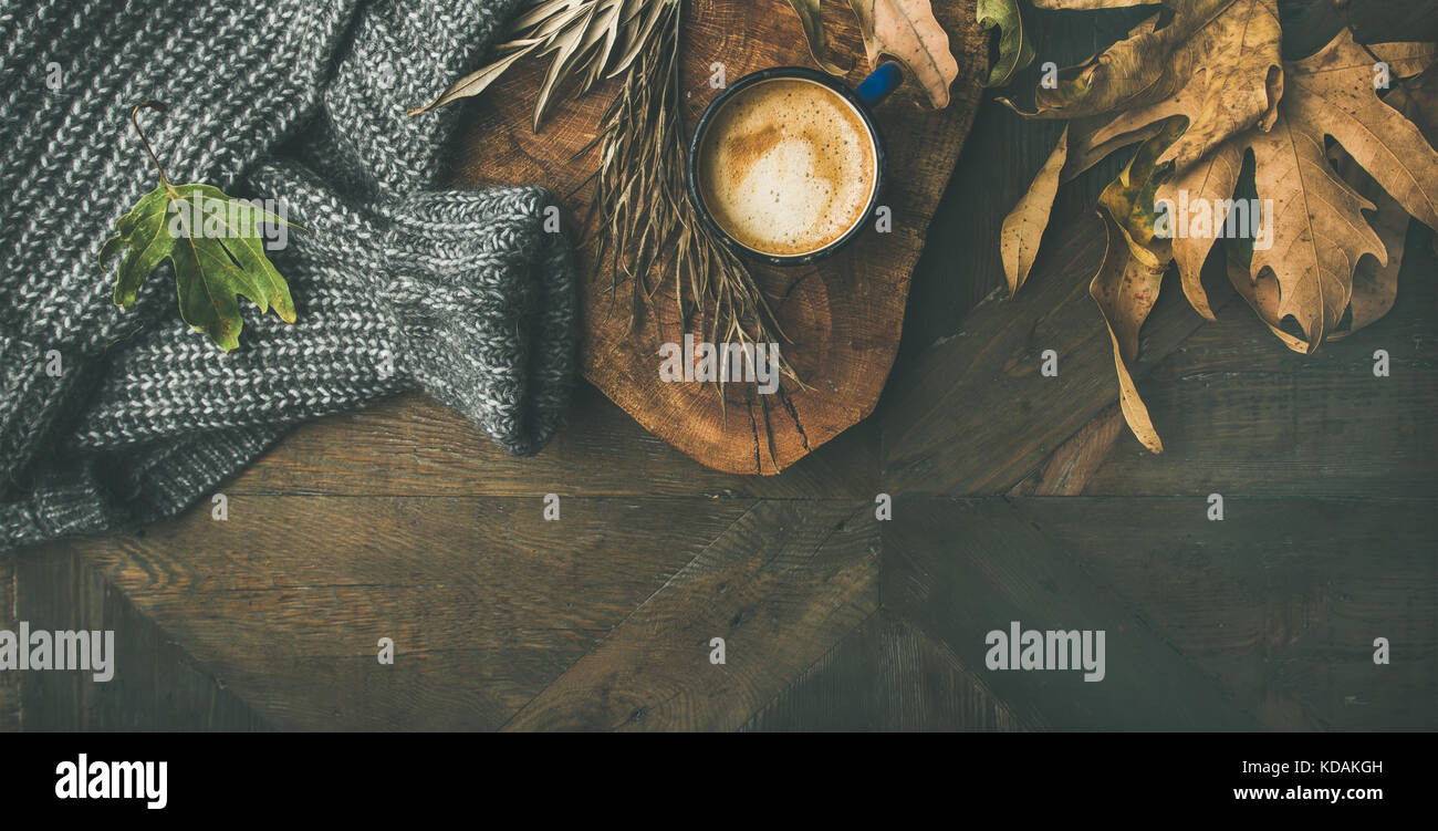 Autumn morning coffee concept with leaves and sweater, copy space - Stock Image