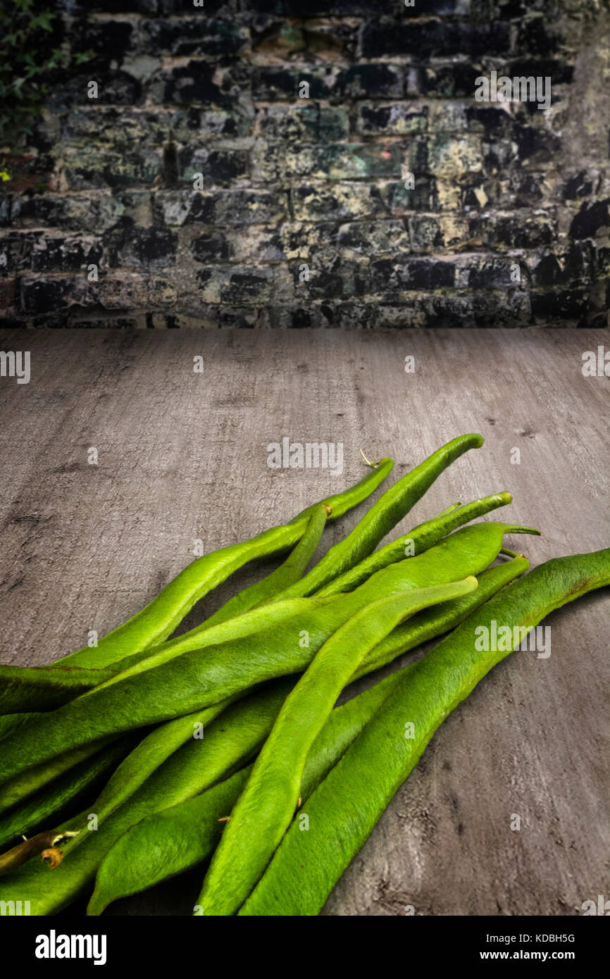 Fresh runner beans on a wooden table - Stock Image