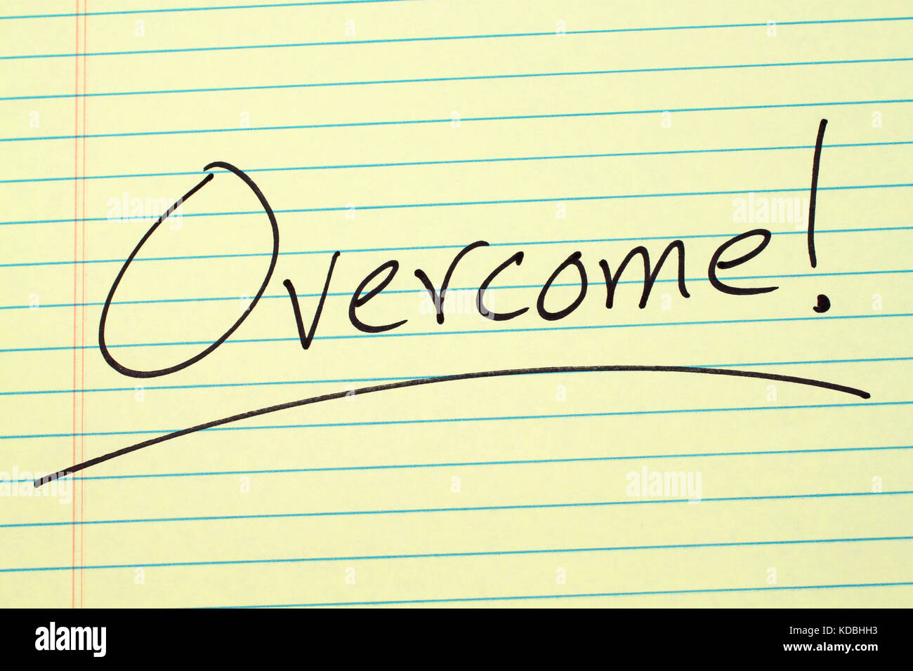 The word 'Overcome!' underlined on a yellow legal pad - Stock Image