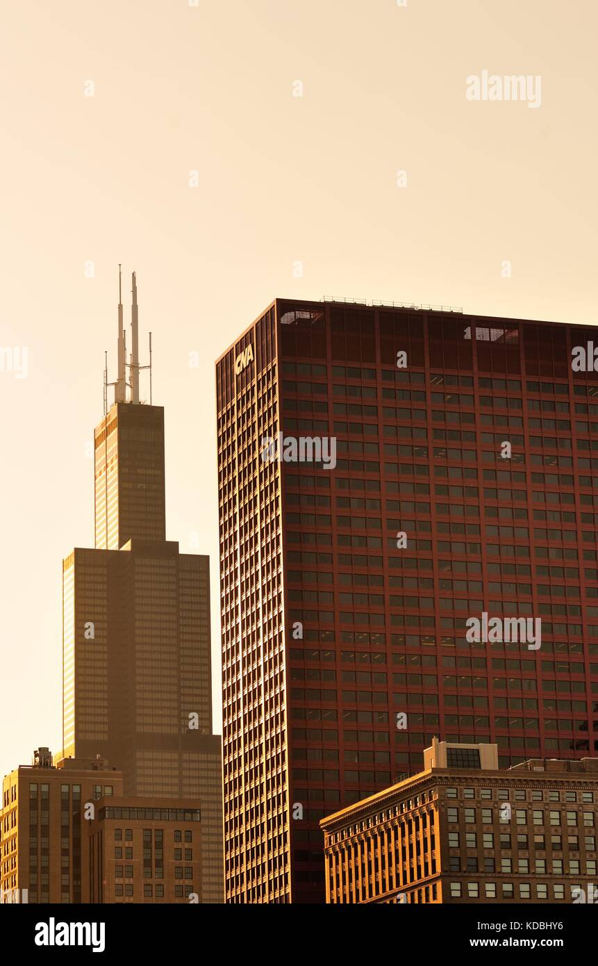 The setting sun illuminates two dominating buildings in this scene of a portion of the Chicago skyline, including, - Stock Image