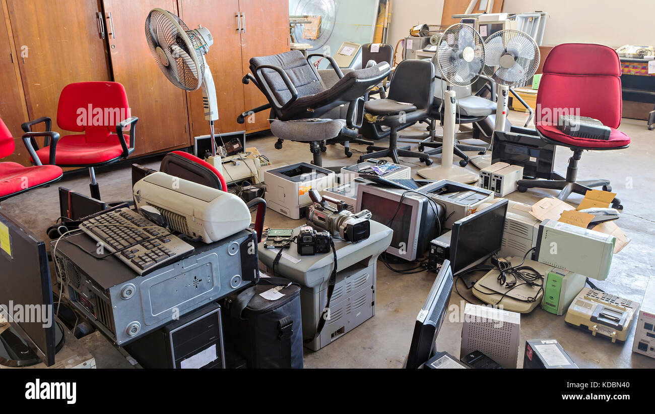 Broken office chairs and electronic waste in the store room - Stock Image