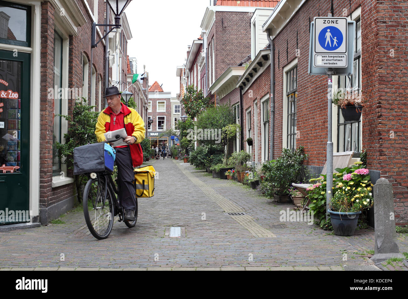 A postal worker delivering mail in a traffic-free street in Haarlem city centre, The Netherlands. - Stock Image