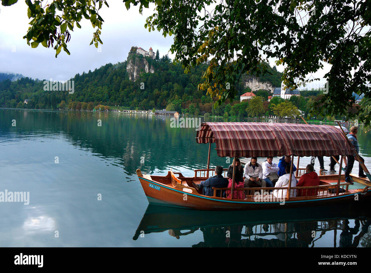 Tourists prepare for a pleasure boat trip round Lake Bled in Bled, Slovenia. In the background is Bled Castle. - Stock Image