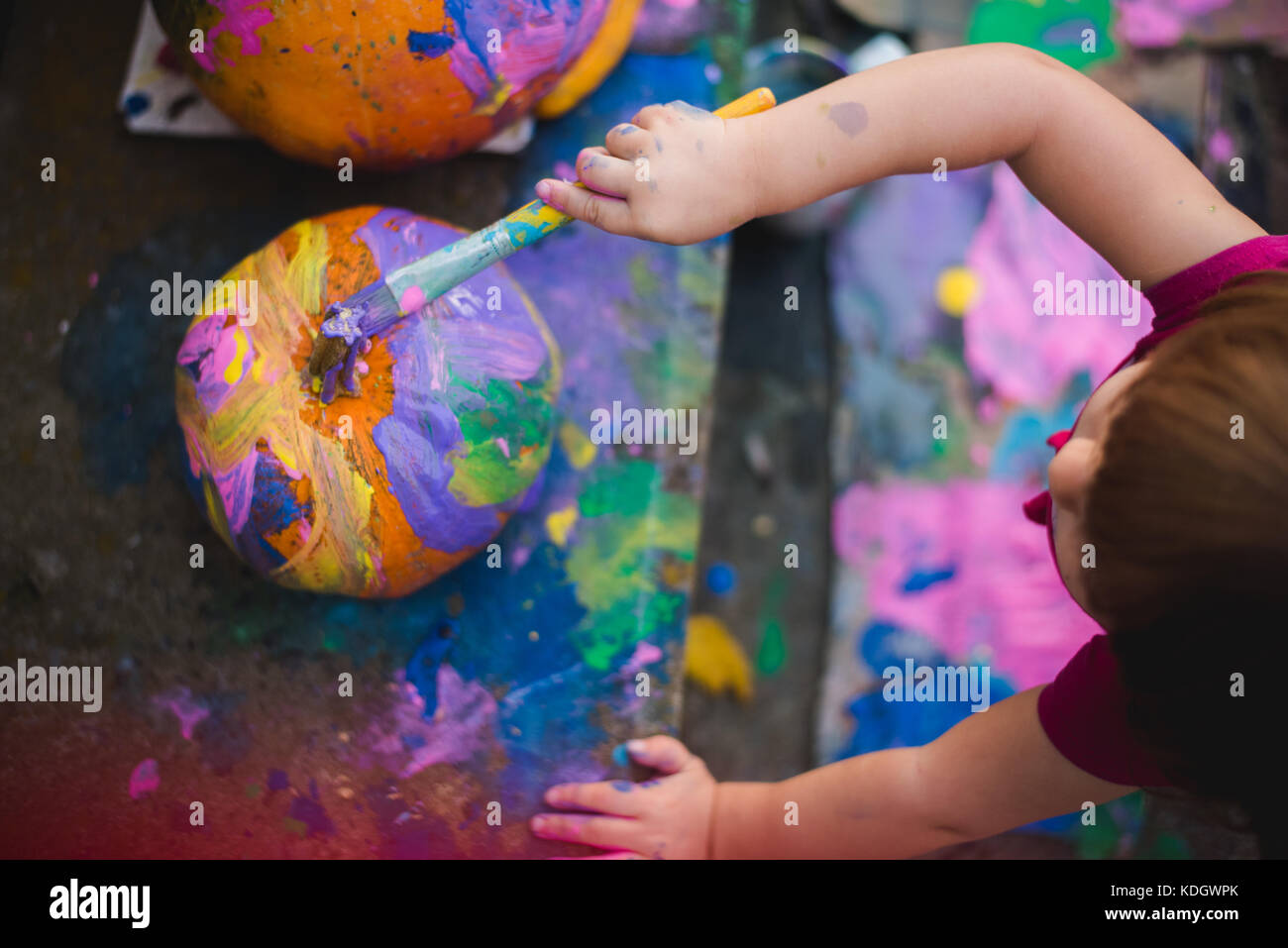 A little girl paints pumpkins during autumn activities. - Stock Image