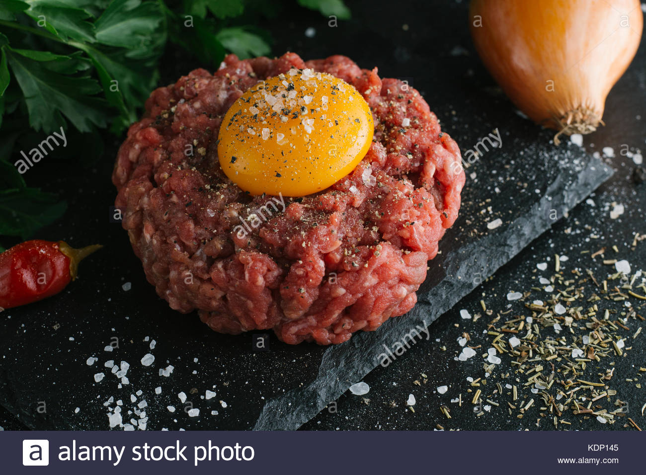 Tartare steak. Beef raw chopped meat with spices, herbs and egg yolk. Fresh, spicy, delicious, gourmet meal on dark - Stock Image