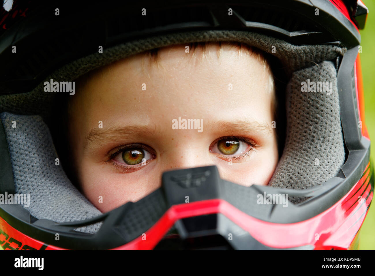 A portrait of a young boy (5 yrs old) wearing a full face cycle crash helmet - Stock Image