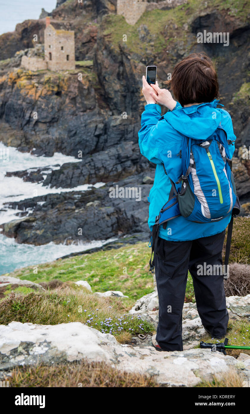 Woman using her mobile phone to take a photograph of the Crown Mines at Botallack in Cornwall, England, UK - Stock Image