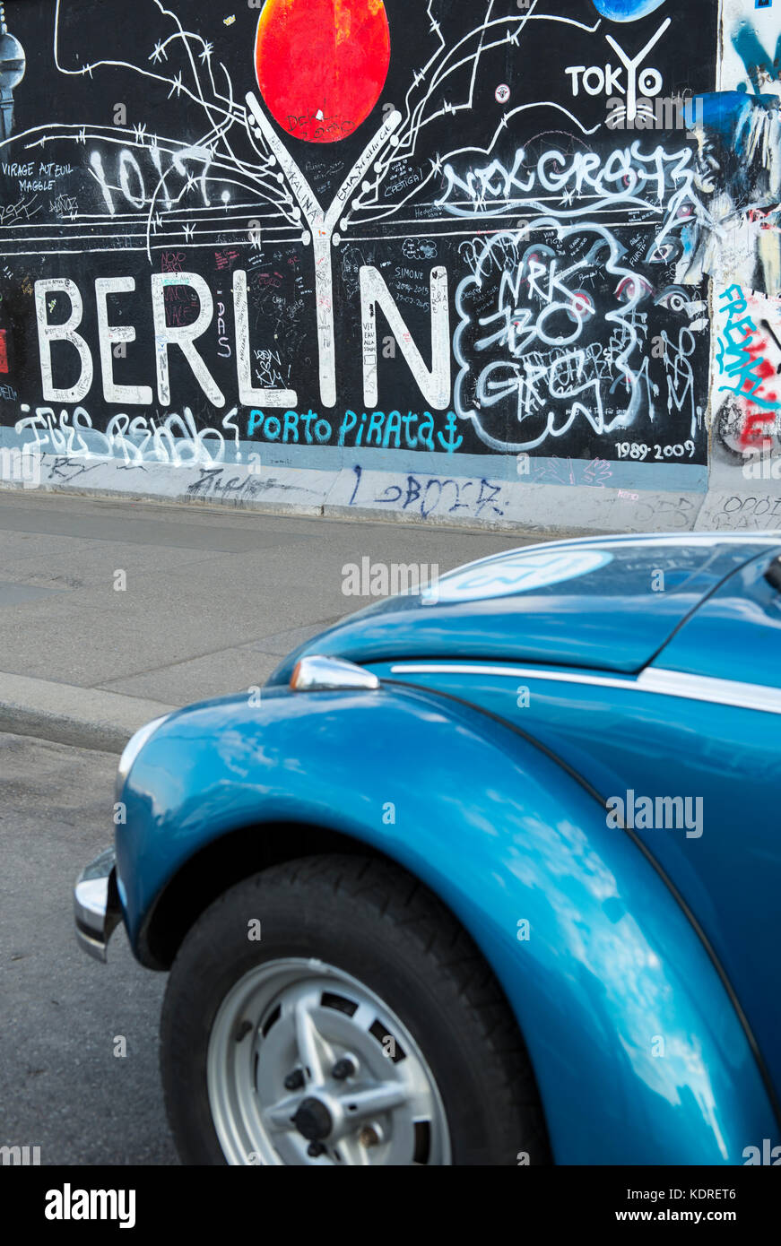 Car parked by the Berlin wall at the East Side Gallery in Berlin, Germany - Stock Image