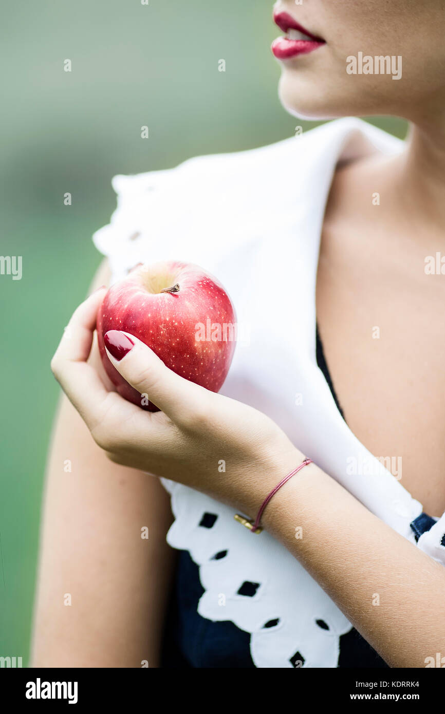 Girl holding a red apple - Stock Image