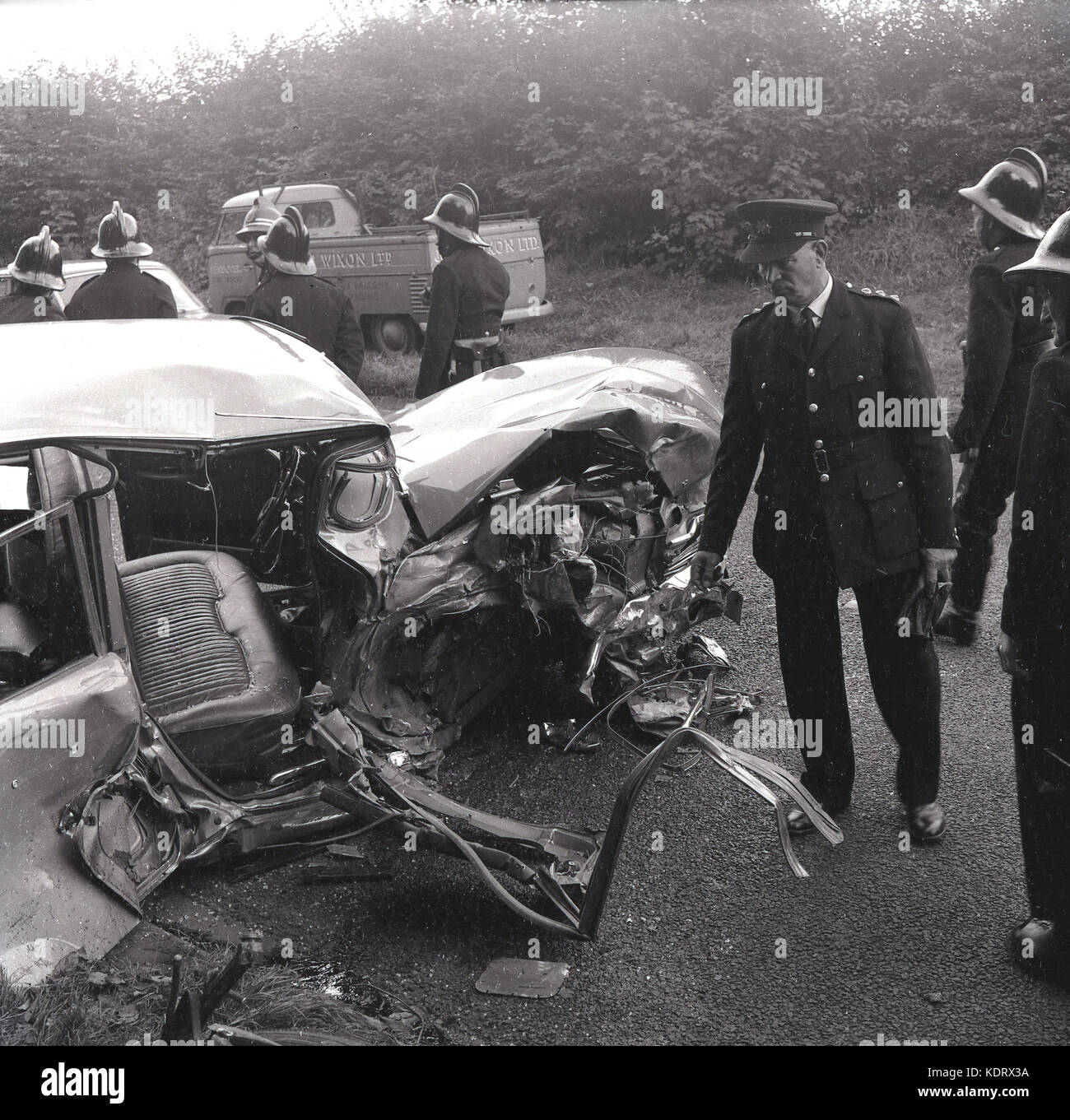 1960s, Buckinghamshire, UK, poiice and firemen with helmets at the scene of a rural road accident and a severely - Stock Image