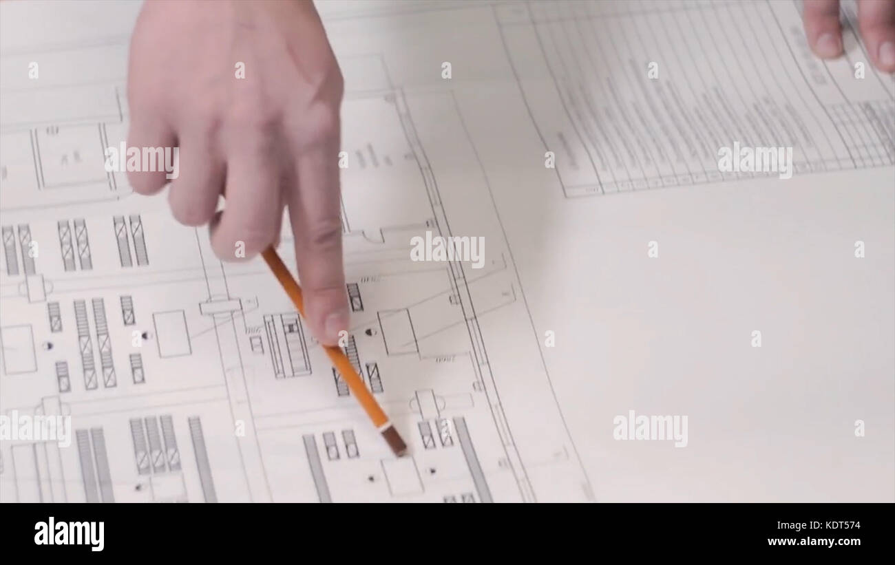 A man shows using a pencil on a drawing or blueprint on the table. Man show construction plans at the table. Business - Stock Image