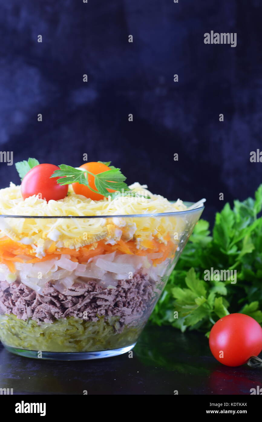 Salad with chicken liver in layers with pickles,boiled carrot, egg, cheese in a glass bowl on a black abstract background. - Stock Image