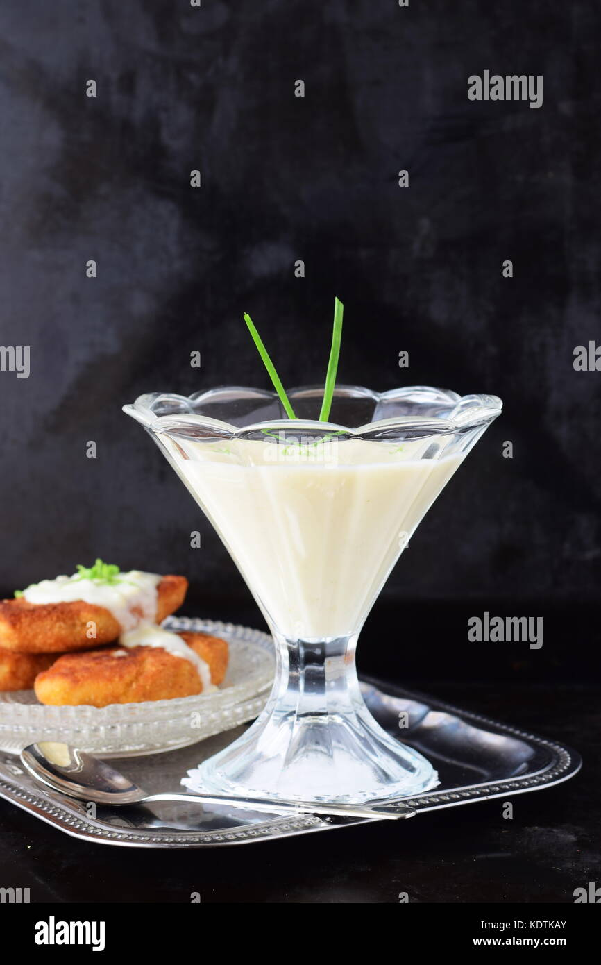 Simple easy to cook milk based gravy in a glass on a metal tray. Healthy food concept - Stock Image