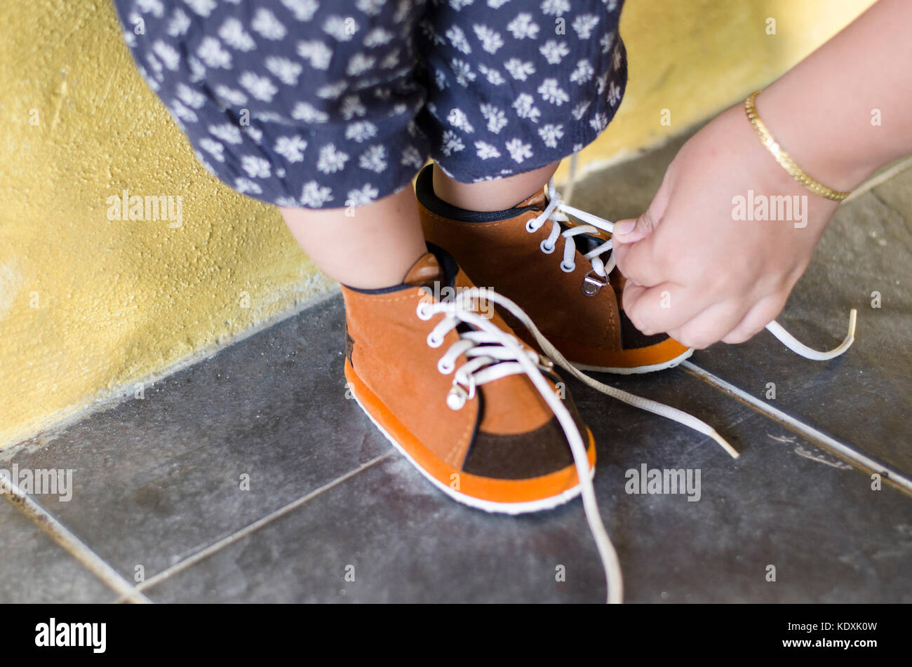mother is tying her daughter shoes. wear brown shoes day. parenting concept - Stock Image