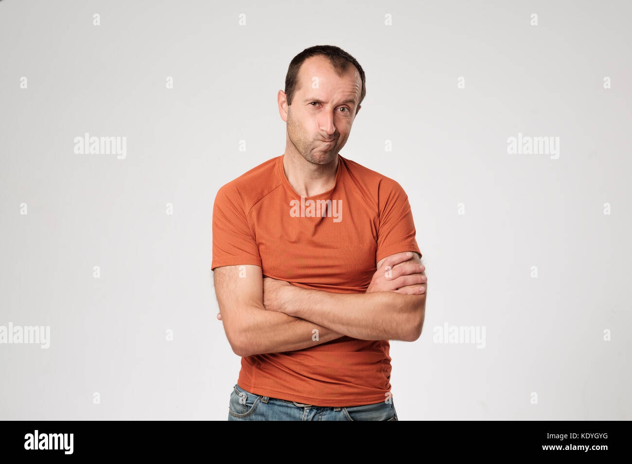 Isolated portrait of angry man wearing orange t-shirt holding arms crossed, having skeptical and dissatisfied look. - Stock Image