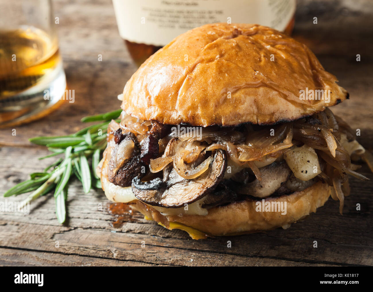 Burger with mushrooms, fried onions and cheese on rustic background - Stock Image