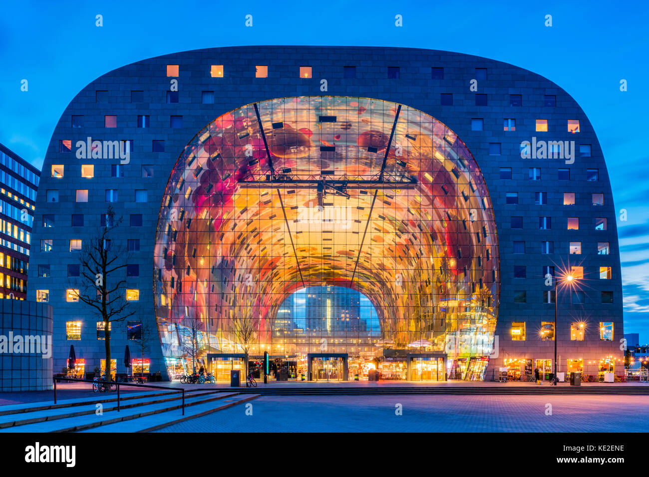 Market Hall in the Blaak district of Rotterdam, Netherlands at dusk. It is a residential and office building with - Stock Image
