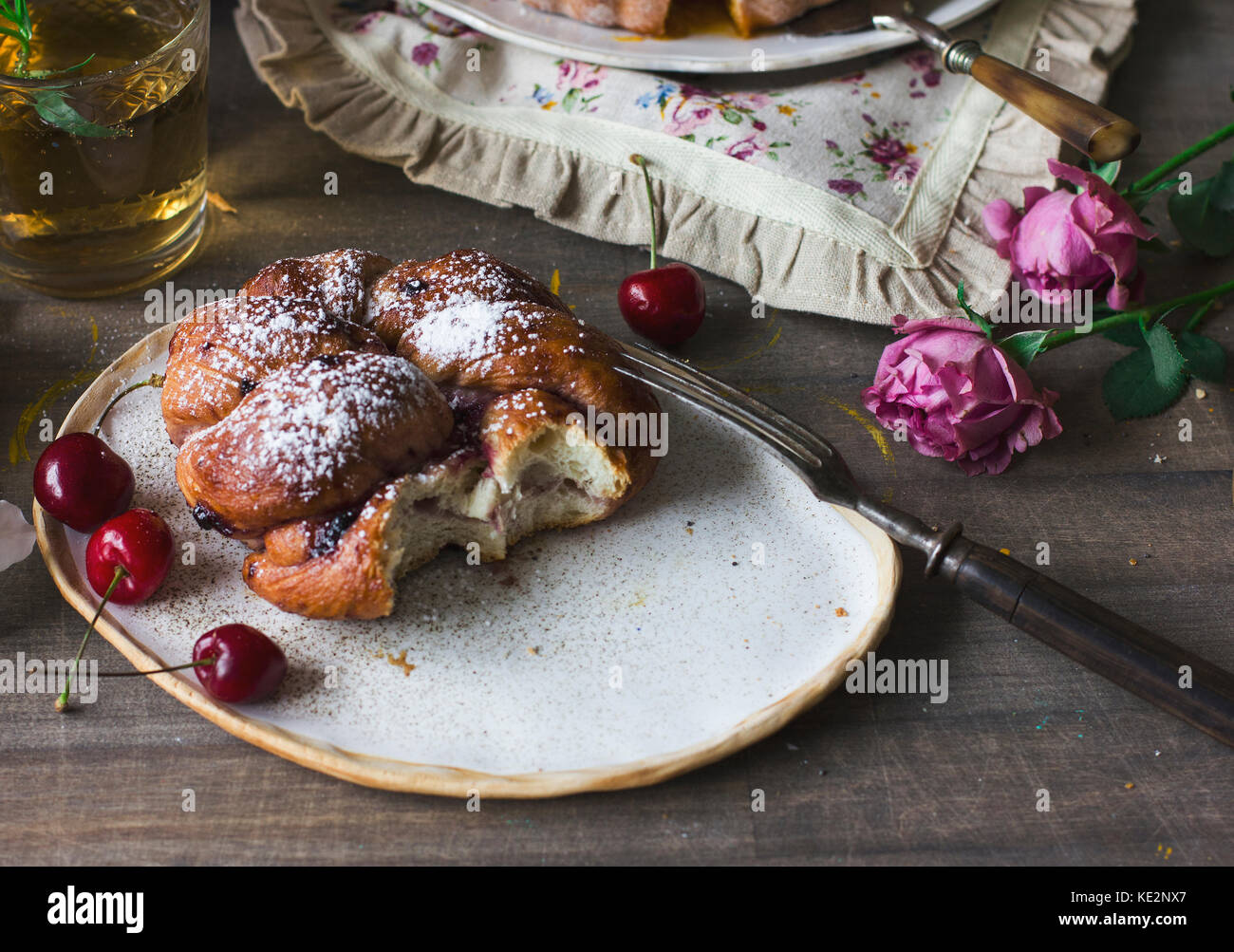 Homemade bun on the plate with cherries - Stock Image